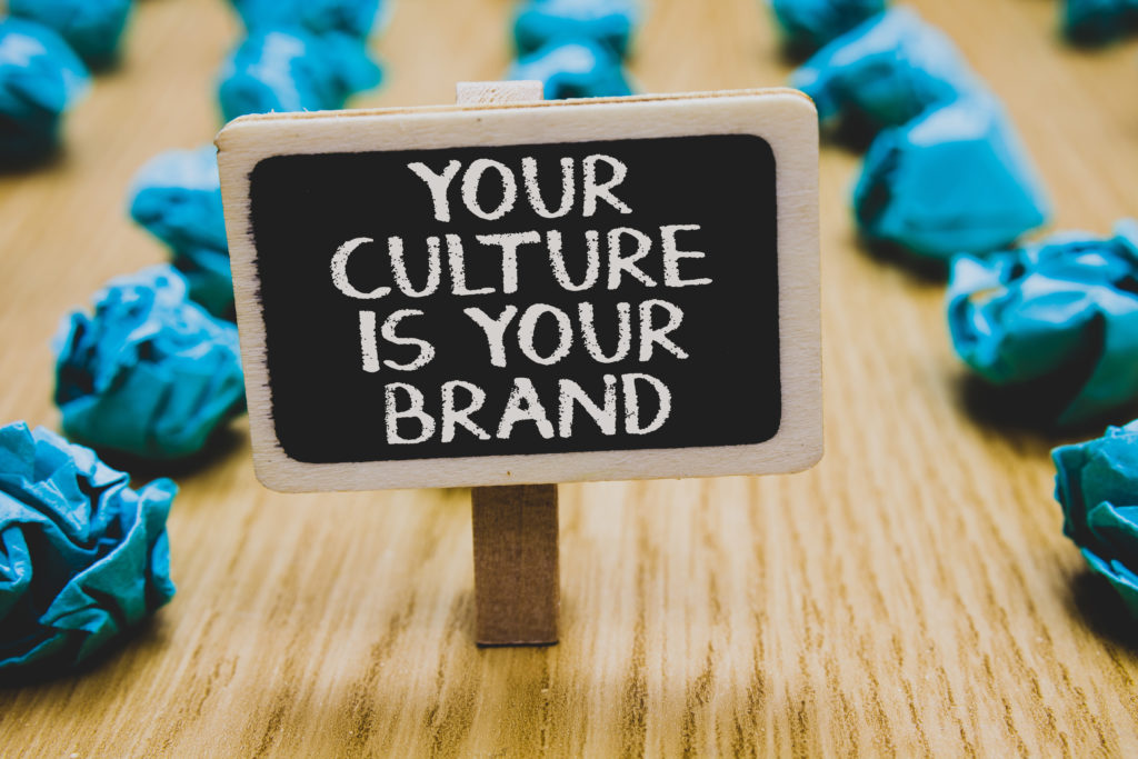 Handwriting text writing Your Culture Is Your Brand. Concept meaning Knowledge Experiences are a presentation card Stand blackboard with white words behind blurry blue paper lobs woody floor